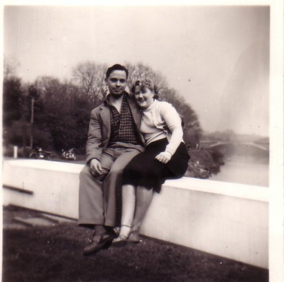 Ron and Sylvia Moss sitting on the arm of the lock gate at Holt Fleet, showing the bridge over the River Severn in the background - early 1950's.